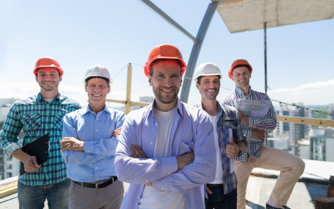 Builders Team Leader Over Group Of Apprentices At Construction Site, Happy Smiling Engineers